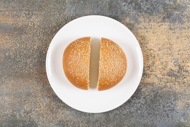 Half gesneden lekker broodje met sesamzaadjes op een witte plaat.
