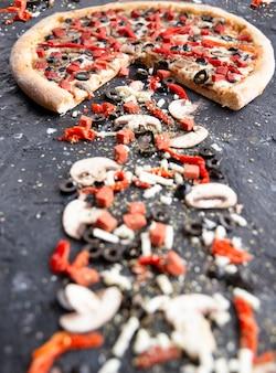 Half gesneden pizza en champignons, rode peper en olijven op een zwart stenen bord