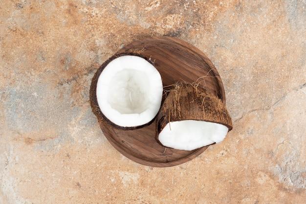 Half gesneden rijpe kokosnoten op houten plaat.