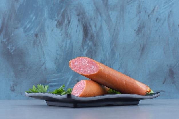 Half gesneden salami op zwarte plaat.