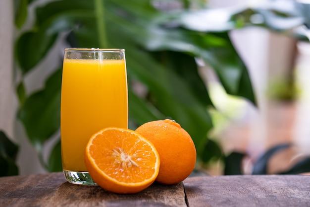 Half gesneden sinaasappel tegen glas sinaasappelsap op houten tafel