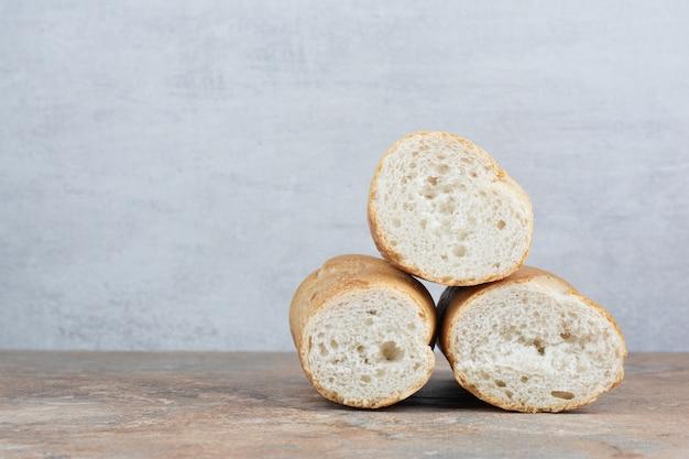 Half gesneden stokbroodbrood op marmeren achtergrond