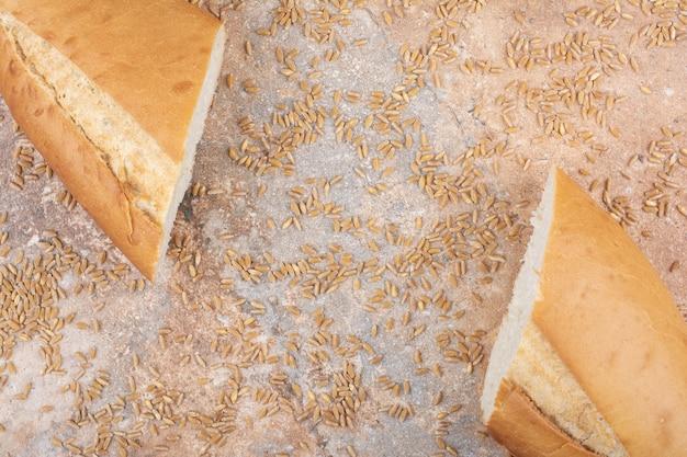 Half gesneden tarwebrood met gerst op marmeren oppervlak