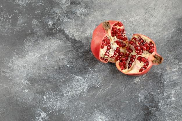 Half gesneden verse granaatappel op marmeren achtergrond.