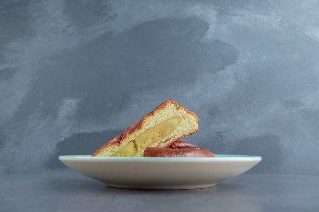 Half gesneden zelfgemaakte gebakjes op blauw bord.
