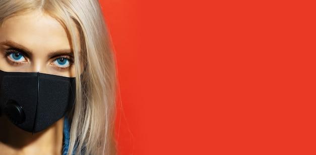Half gezicht portret van een jong meisje met blauwe ogen en blond haar, gekleed in zwart, respiratoir gezichtsmasker tegen coronavirus, achtergrond van rode kleur met kopie ruimte.