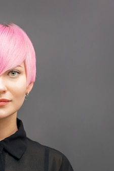 Half gezicht portret van een mooie jonge blanke vrouw met kort helder roze kapsel.