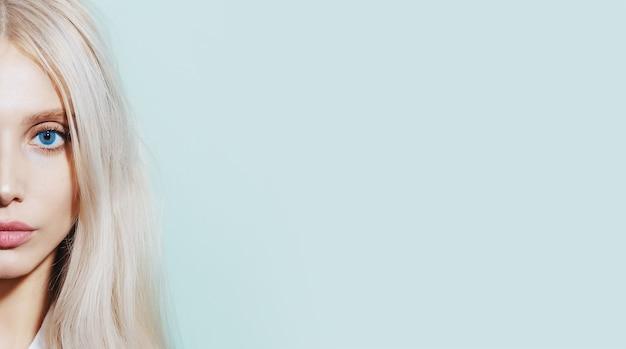 Half gezicht portret van jonge blonde vrouw op cyaan oppervlak