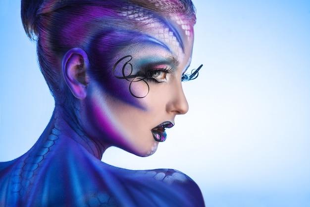 Half gezicht portret van sexy mannequin met creatieve make-up. wegkijken op blauw