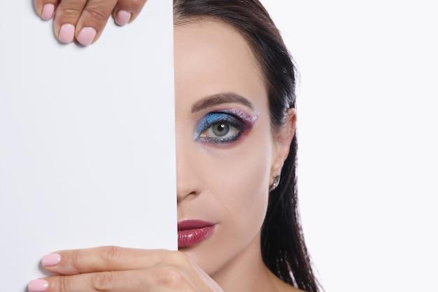 Half gezicht van jonge sexy vrouw met bordeauxrode lippenstift en heldere oogmake-up klassieke make-up en