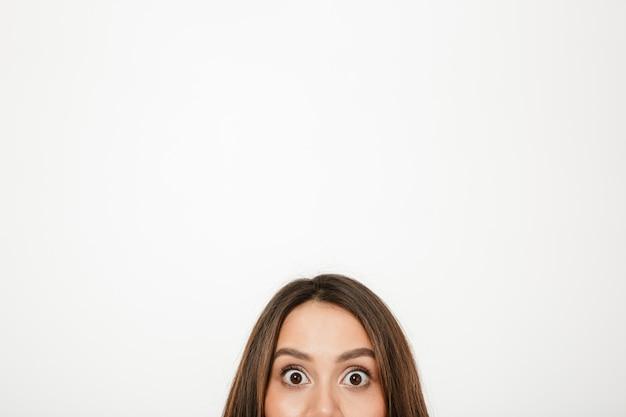 Half gezicht van verraste donkerbruine vrouw die de camera over grijs bekijkt