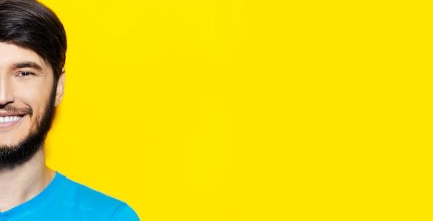Half gezichtsportret van jonge glimlachende kerel op oppervlakte van gele kleur