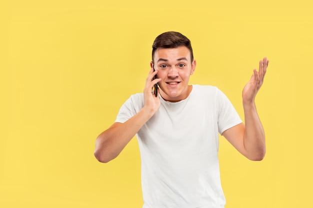 Half-lengteportret van de kaukasische jonge man op gele muur
