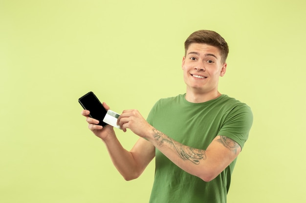Half-lengteportret van de kaukasische jonge man op groene studioachtergrond. mooi mannelijk model in overhemd. concept van menselijke emoties, gezichtsuitdrukking, verkoop, advertentie. telefoon en kaart vasthouden, online betalingen.