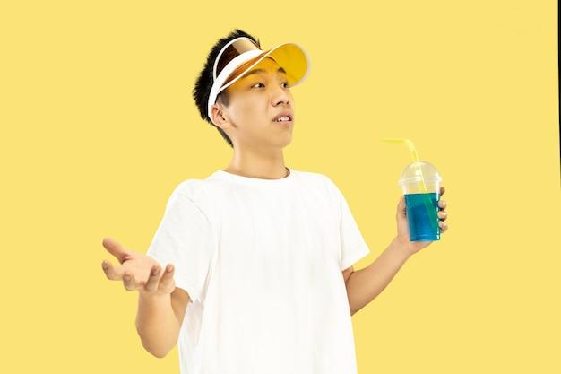 Half-lengteportret van de koreaanse jongeman op gele muur