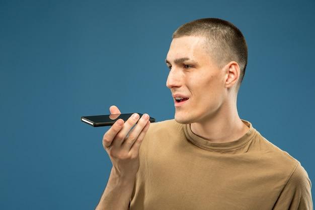 Half-length portret van een blanke jonge man op blauwe studio achtergrond. mooi mannelijk model in overhemd. concept van menselijke emoties, gezichtsuitdrukking, verkoop, advertentie. copyspace. spraakbericht opnemen.