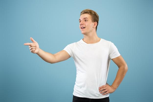 Half-length portret van een blanke jonge man op blauwe studio