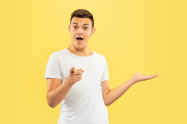 Half-length portret van een blanke jonge man op gele studio
