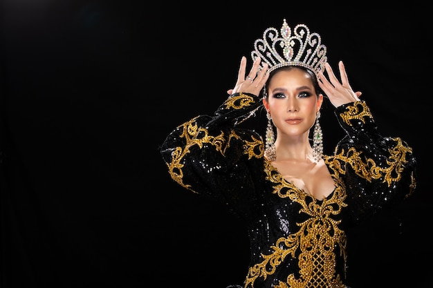 Half lichaam portret van aziatische transgender vrouw in cabaret carnaval fancy zwart goud koningin jurk jurk diamanten kroon over donkere achtergrond