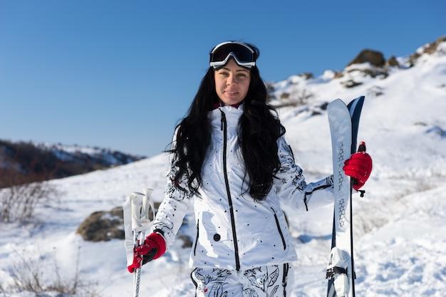 Half lichaam shot van een sportieve vrouw in ski-uitrusting met uitrusting tegen bergresort.