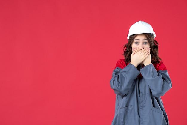 Half lichaamsschot van bange vrouwelijke bouwer in uniform met helm op geïsoleerde rode achtergrond