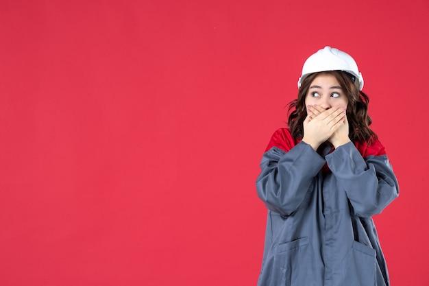 Half lichaamsschot van geschokte nieuwsgierige vrouwelijke bouwer in uniform met helm op geïsoleerde rode achtergrond