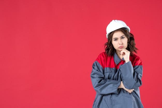 Half lichaamsschot van ondervragende vrouwelijke bouwer in uniform met helm en geconcentreerd op iets op geïsoleerde rode achtergrond