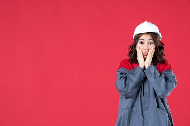 Half lichaamsschot van onzekere emotionele vrouwelijke bouwer in uniform met helm op geïsoleerde rode achtergrond