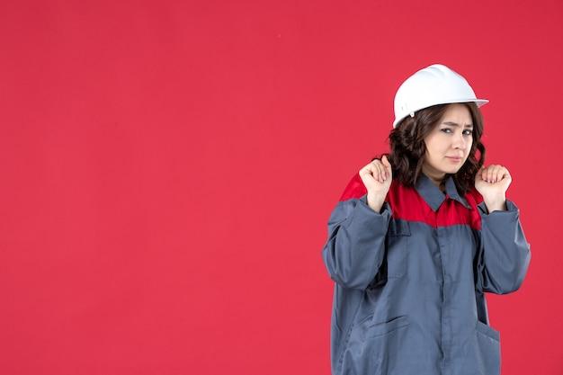 Half lichaamsschot van verraste vrouwelijke bouwer in uniform met helm op geïsoleerde rode achtergrond