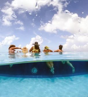 Half onderwater gesplitst beeld van jonge vrouwen die plezier hebben in het hotelzwembad in het concept van de caribische zee