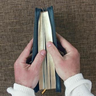 Half open bijbel in zijn hand