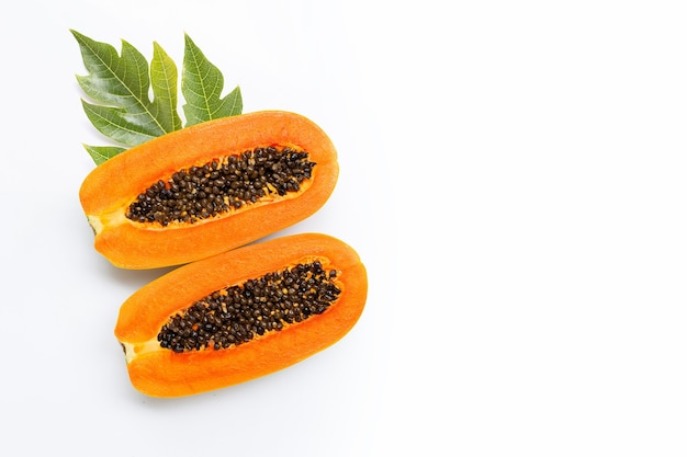 Half papajafruit met blad op witte achtergrond.