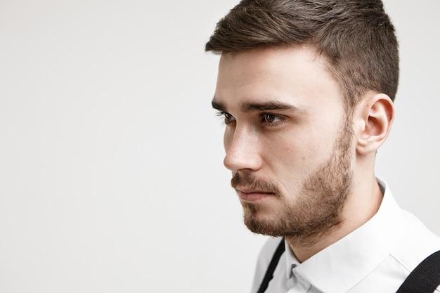Half profiel close-up beeld van zelfbepaalde gerichte jonge kaukasische ongeschoren zakenman in formele kleding poseren tegen witte studio muur achtergrond met copyspace voor uw tekst of inhoud