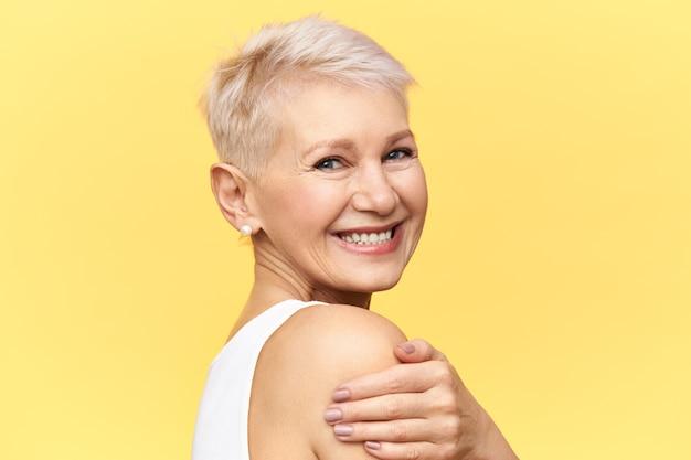 Half profiel portret van vrolijke gelukkig mooie gepensioneerde vrouw met plezier, geïsoleerd poseren, zichzelf omhelzen, camera kijken met vrolijke glimlach