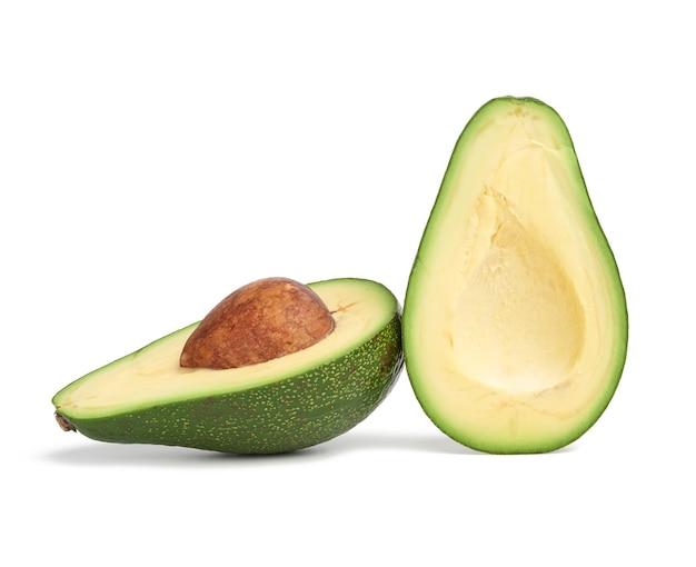 Half rijpe groene avocado met een bruine steen geïsoleerd op een wit
