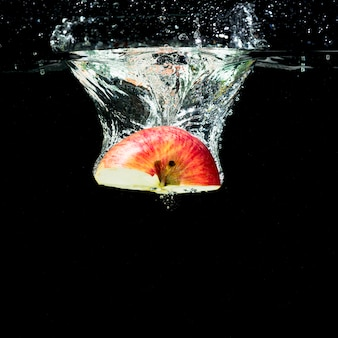 Half rode appel vallen in water met bubbels tegen zwarte achtergrond