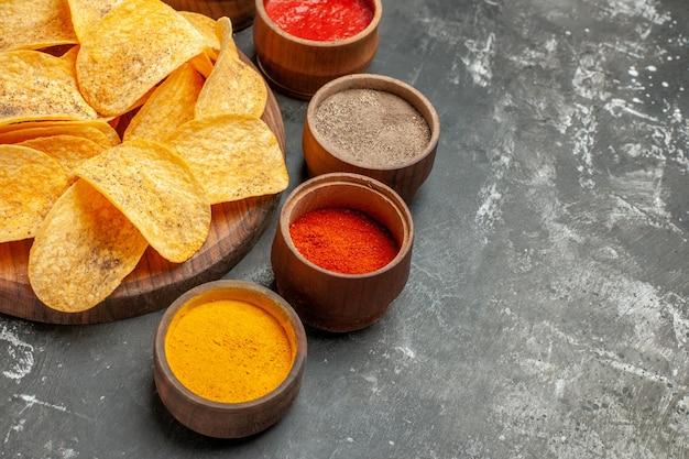 Half schot van chips, kruiden en mayonaise met ketchup op houten snijplank op grijze tafel