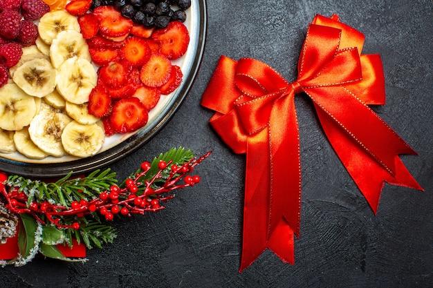 Half schot van de collectie van vers fruit op de accessoires van de dinerborddecoratie dennentakken en cijfers op een rood servet en een rood lint