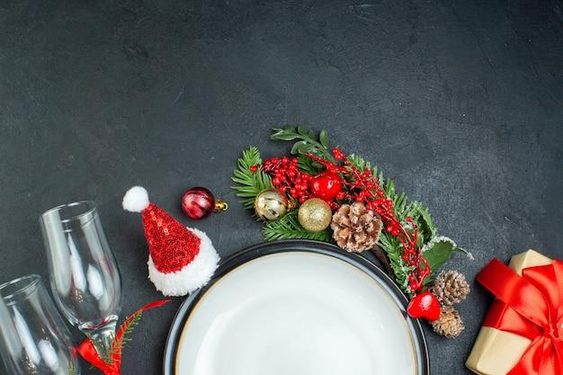 Half schot van diner plaat kerstboom fir takken conifer kegel geschenkdoos kerstman hoed gevallen glazen bekers op zwarte achtergrond