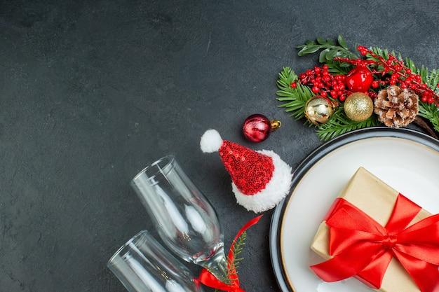 Half schot van geschenkdoos op diner plaat kerstboom fir takken conifer kegel kerstman hoed gevallen glazen bekers op zwarte achtergrond