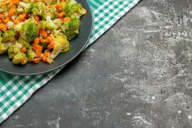 Half schot van gezonde groentesalade op groene gestripte handdoek op grijze tafel