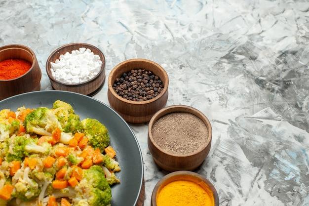 Half schot van gezonde groentesalade op houten snijplank en kruiden op witte tafel