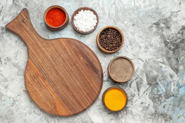 Half schot van gezonde houten snijplank verschillende kruiden op witte tafel