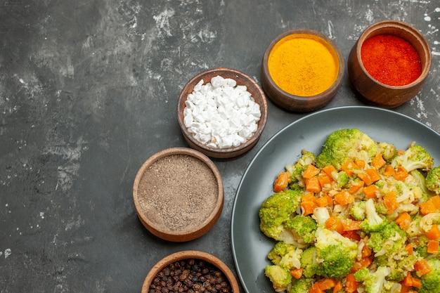 Half schot van gezonde maaltijd met brocoli en wortelen op een zwarte plaat en kruiden op grijze tafel