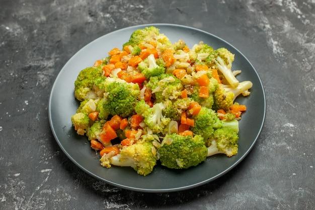 Half schot van gezonde maaltijd met brocoli en wortelen op een zwarte plaat op grijze tafel