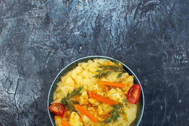 Half schot van heerlijke aardappelmaaltijd met verse groenten op de bodem op donkere kleurenachtergrond met vrije ruimte