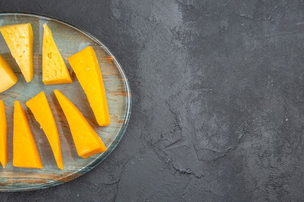 Half schot van heerlijke gesneden kaas op een blauw bord op zwarte achtergrond