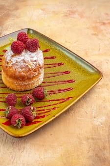 Half schot van heerlijke minicake met fruit op een groene plaat op gemengde kleurenachtergrond