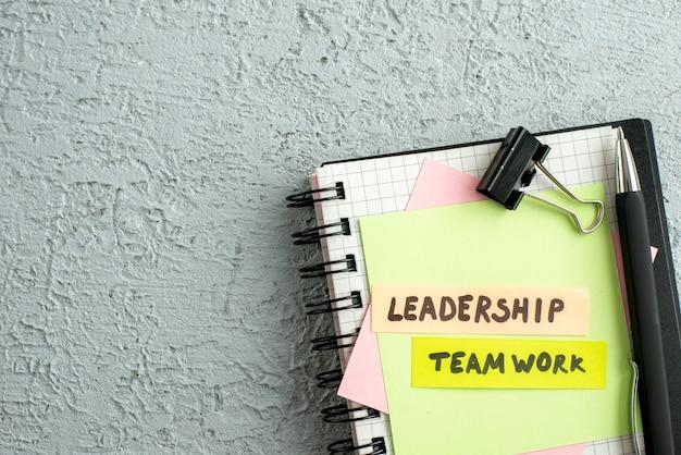 Half schot van leiderschapsteamwork op gekleurde enveloppen op spiraalvormig notitieboekje en boek op grijze zandachtergrond