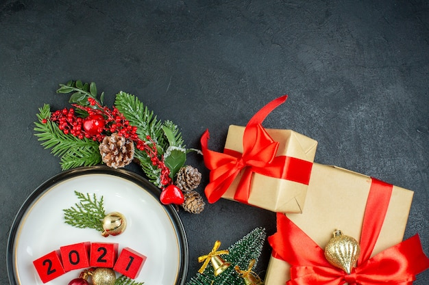 Half schot van nummers decoratie accessoires op een plaat fir takken conifer kegel kerstboom geschenkdozen op donkere achtergrond